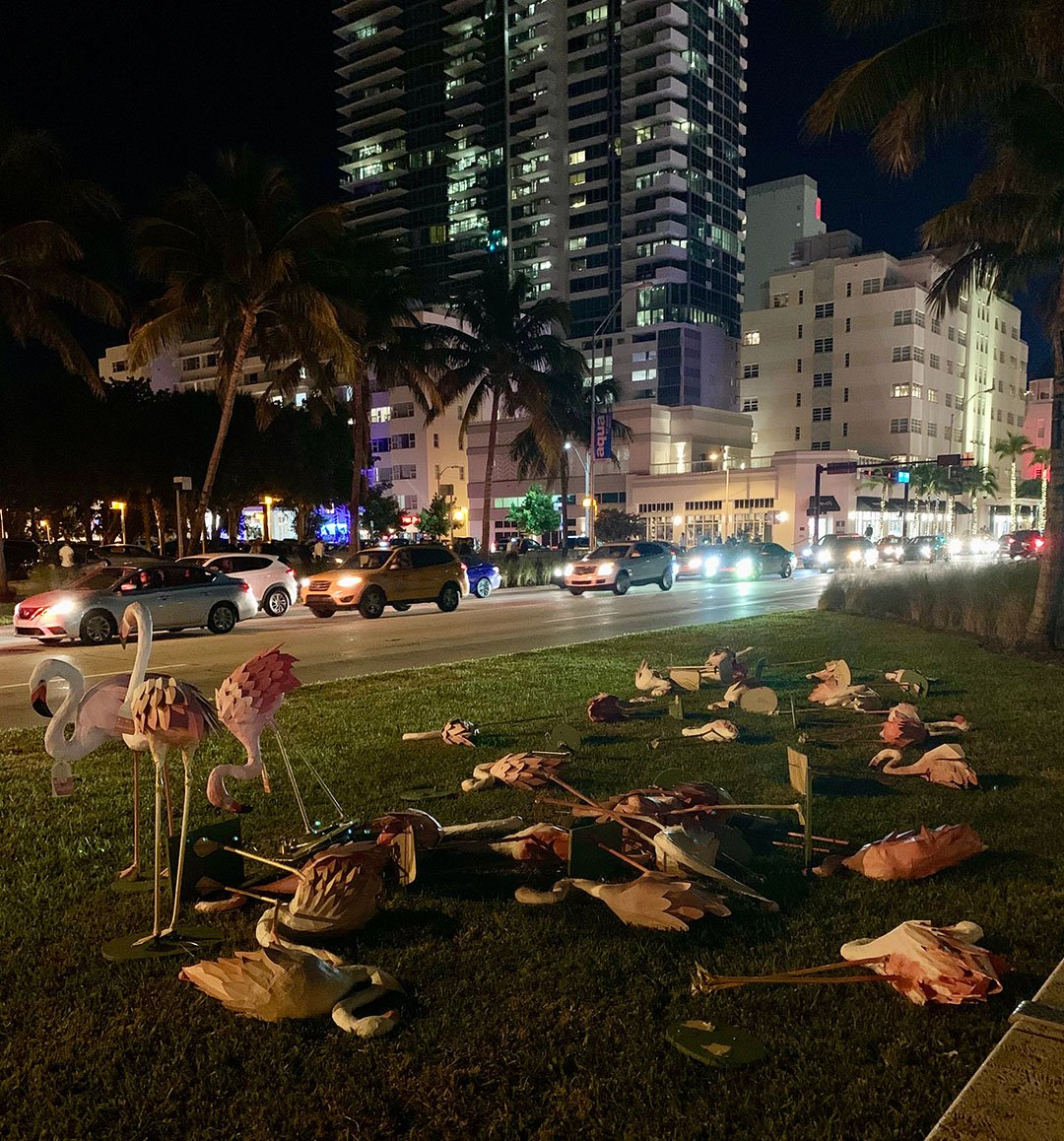 Miami street at night with Flamingo sculpture art on lawn