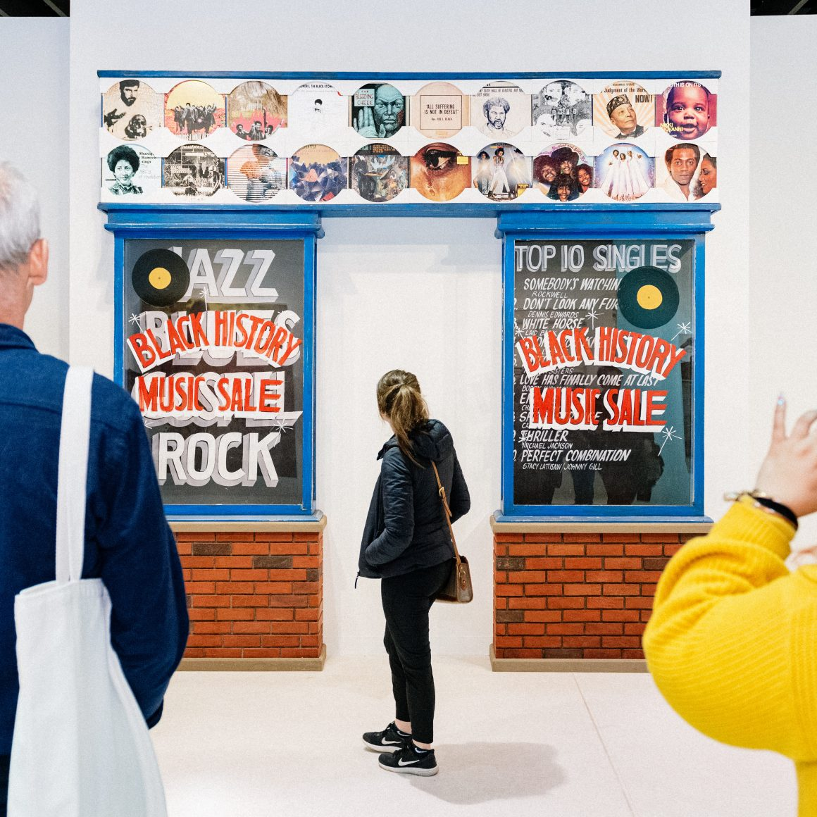 """Photo of a person looking an a piece of art of a store front which reads """"Black History Music Sale"""""""